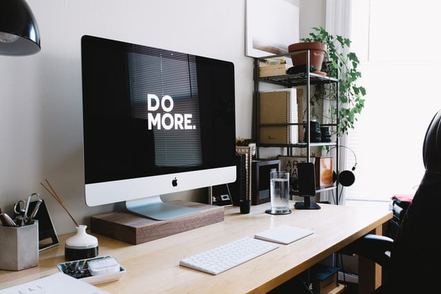 """Photo of iMac on desk, with """"DO MORE"""" on the screen. Tidy office set-up surrounds the computer."""